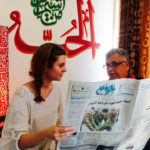 Student reading the Amman newspaper with her teacher