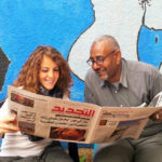 student reading the Rabat newspaper with her teacher